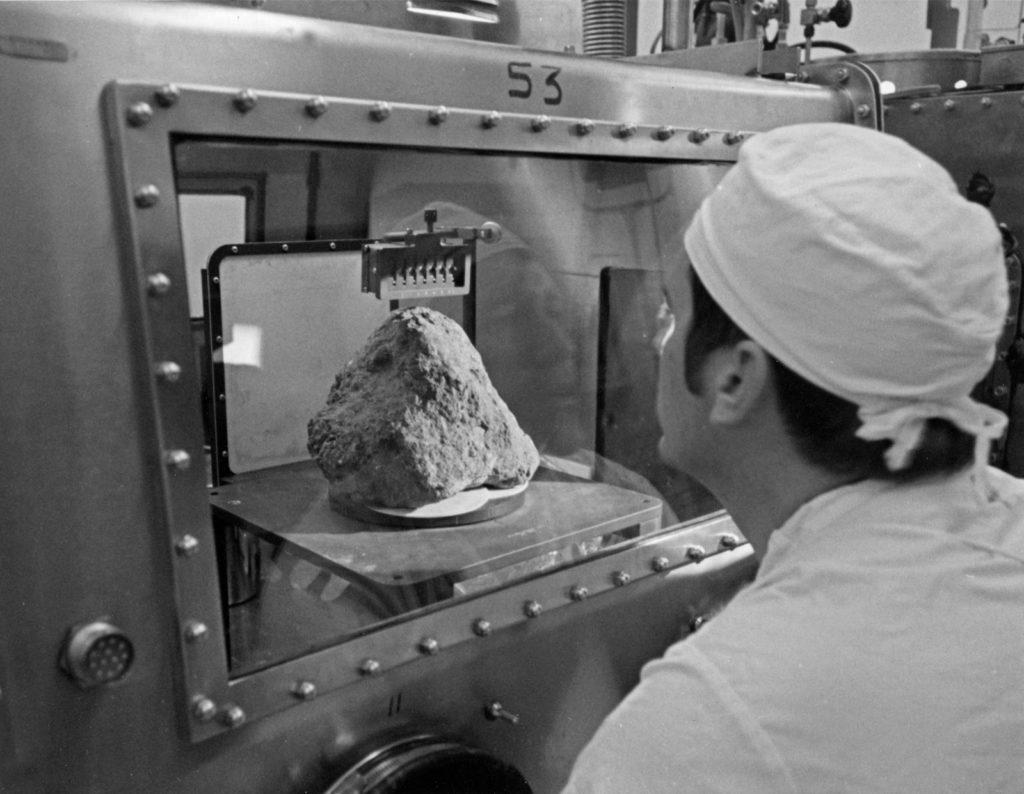Аполлон 14, лунный образец. Лаборант, исследующий лунный образец, называемый Большой Бертой, который был собран во время миссии Аполлон-14