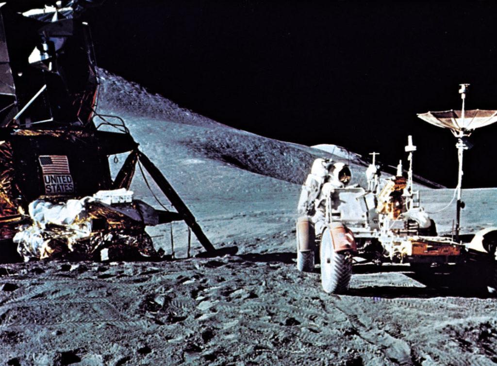 Аполлон 15. Астронавт Аполлона-15 Джеймс Б. Ирвин, стоящий позади Лунного передвижного корабля; лунный модуль (LM) находится слева, а перед ним находится модульная сборка оборудования (MESA). Аполлон 15 был выпущен 26 июля 1971 года.