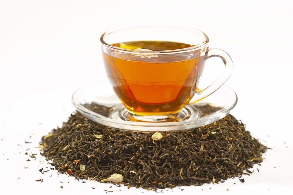 Чашка черного чая поверх чайных листьев