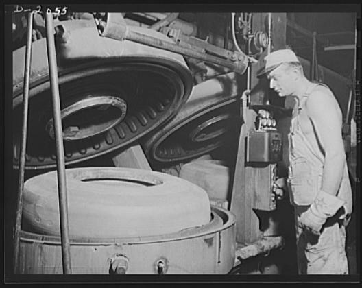 Рабочий, помещающий шину в форму перед вулканизацией